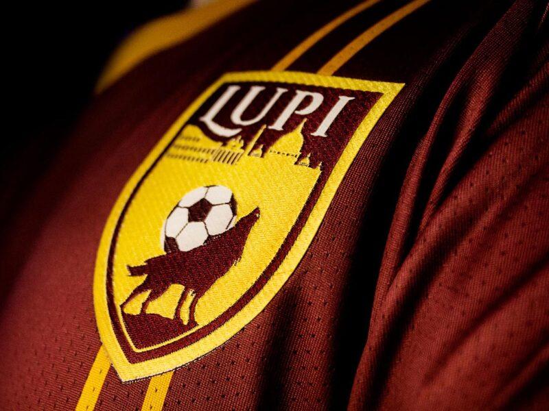 Stemma di lupo con pallone e skyline di Roma su maglietta di calcio a 5